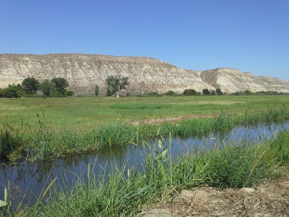 Across Highway 52 to the north, working ranches, community irrigation canals, and distantly recognizable sandstone cliffs and bluffs lie in close proximity to the directionally drilled and potentially fracked Smoke Ranch natural gas well, within a river confluence and wetlands floodplain.