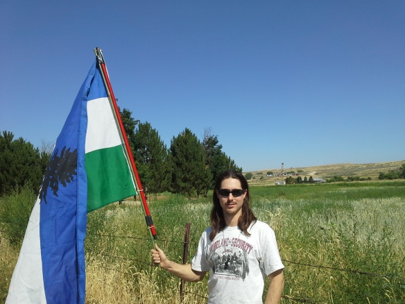 Indigenous activist and defender of wolves, Mato Woksape, flies the Cascadia flag at the last stop of a great educational and expressive event, as concerned Idaho citizens converge along Little Willow Road, to view the drilling derrick and operations of the ML Investments 2-10 well, situated on a private road and property.