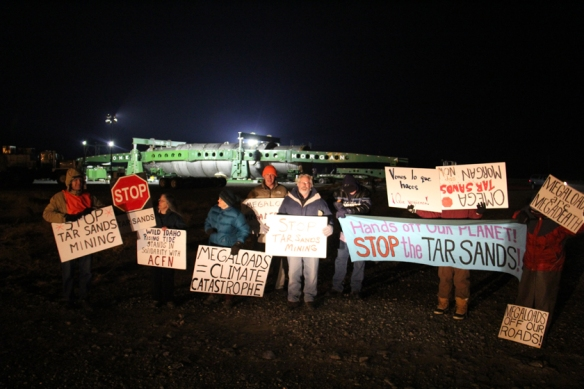 Protesters demonstrating against a megaload bound for a tar sands mining site in Canada gather in front of it at the Port of Umatilla on Sunday evening. The 300-foot-long, 20-foot-high transport scheduled to travel through Hermiston on Monday night has been rescheduled to leave on Sunday, December 1 (Hermiston Herald/Colin Murphey photo).