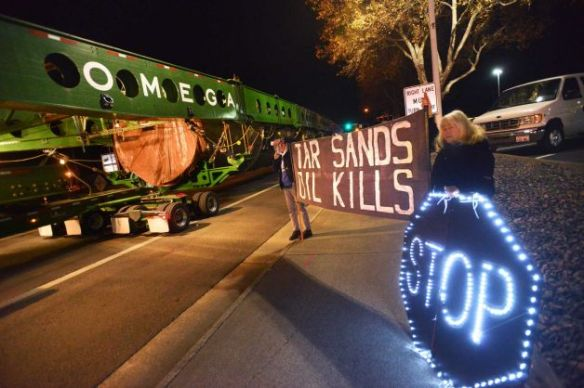 On Monday, December 2, 2013, light brigade action team protesters Rod Lyman and Kathy Leathers of Bellingham, Washington, hold up signs, as a megaload slowly passes by on Highway 395 in Hermiston, Oregon.  The transport rig carries a 450-ton piece of equipment bound for a tar sands development site in western Canada (Associated Press/E.J. Harris photo).