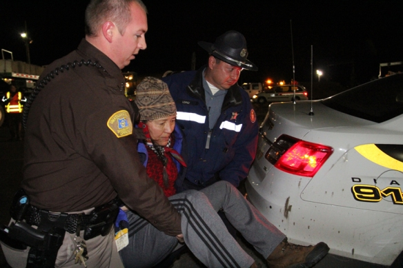 Law enforcement officers carry Cathy Sampson-Kruse to a patrol car, before placing her under arrest for disorderly conduct on Monday at the Port of Umatilla. Sampson-Kruse laid down in front of the megaload truck, in an attempt to prevent its departure. The megaload is currently stalled on Highway 395 south of Pendleton by weather (Hermiston Herald/Colin Murphey photo).
